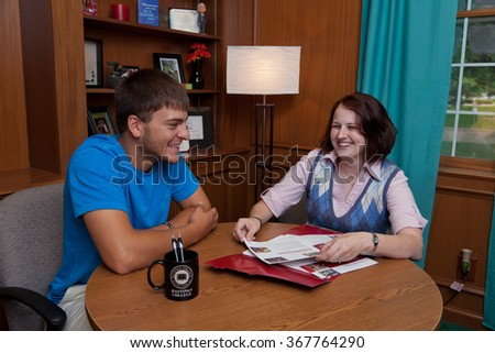 HASTINGS, NE - August 17th, 2013 - A student meets with a professor on the Hastings College campus. The school a private, undergraduate, four-year, religious liberal arts college.  - stock photo