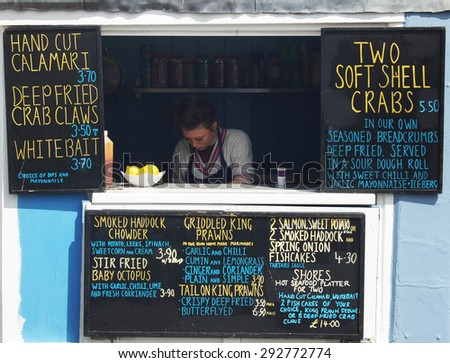 HASTINGS, UK - MAY 04, 2015: Busy staff works in a small seafood shop during the Jack the Green festival in Hastings,UK. - stock photo
