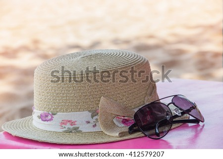 Hat and glasses on the table at the beach,summer concept.