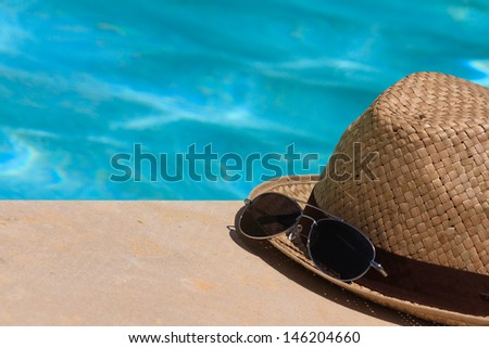 hat and sunglasses by the pool - stock photo