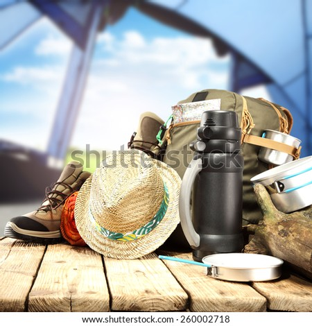 hat backpack and wooden table in tent  - stock photo