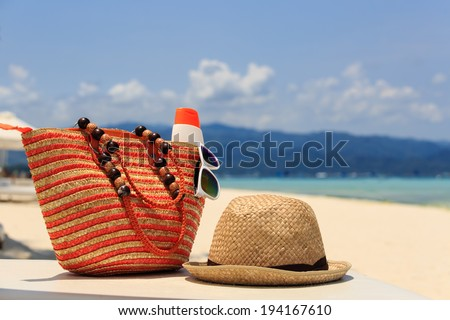 hat, bag, sun glasses and flip flops on a tropical beach, vacation concept