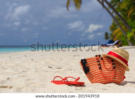 hat, bag, sun glasses and flip flops on a tropical beach, vacation concept - stock photo