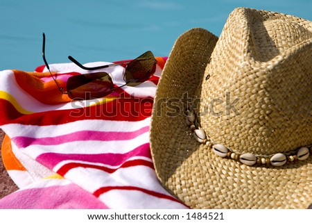 Hat, glasses and towel by a pool - stock photo