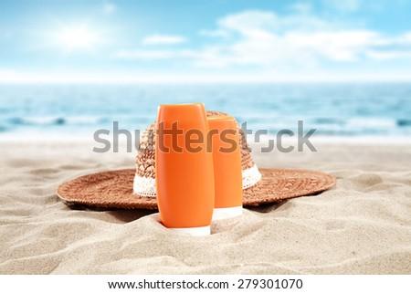 hat on sand and suntan oil  - stock photo