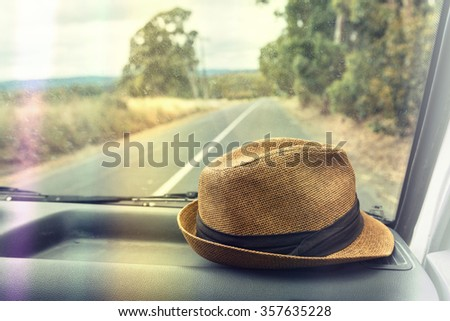 hat on the dashboard of a car on a road trip - stock photo
