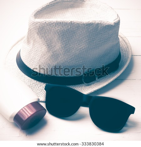 hat sunglasses and body lotion over white table vintage style - stock photo