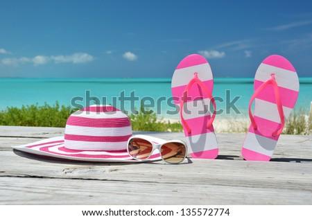 Hat, sunglasses and flip-flops against ocean. Exuma, Bahamas - stock photo