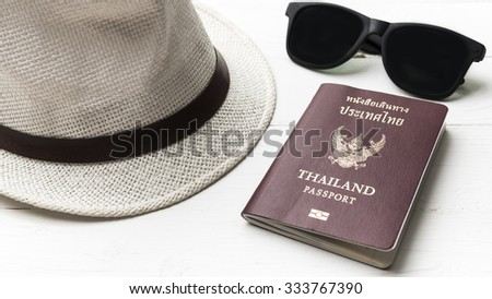 hat sunglasses and passport on white table
