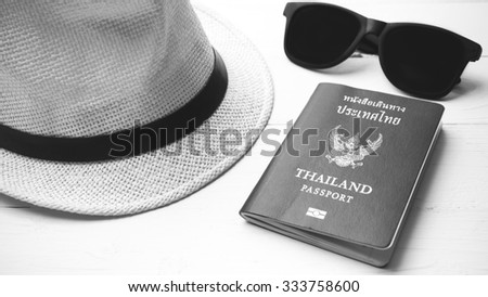 hat sunglasses and passport on white table black and white color