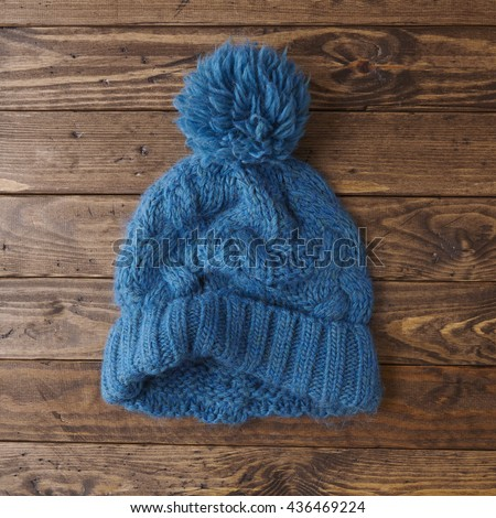 Hats and accessories - a blue, knitted wool, bobble beanie with pom pom on a distressed wood table top background - stock photo