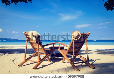 hats on chairs of tropical sand beach - stock photo