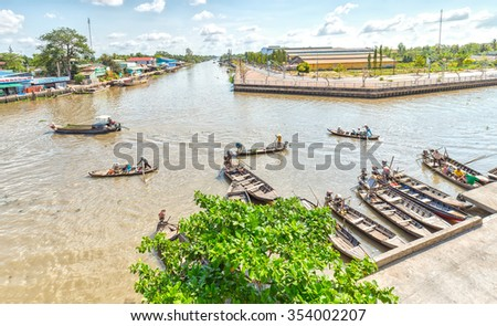 Hau Giang, Vietnam - April 6th, 2015: Panorama wharf floating market with boats gathered waiting passenger, far away passenger barge across river to go in floating market in Hau Giang, Vietnam