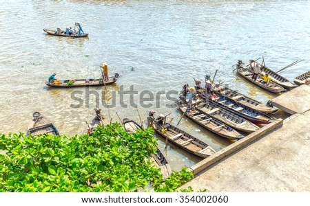 Hau Giang, Vietnam - April 6th, 2015: Wharf floating market with boats gathered waiting passenger, far away passenger barge across the river to go in the morning floating market in Hau Giang, Vietnam