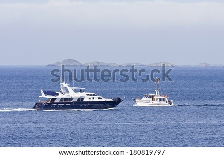 HAUGESUND ARCHIPELAGO, NORWAY - JULY 04. In Excess meets a white Cruiser in the inlet on July 04, 2010. Islands in the background.