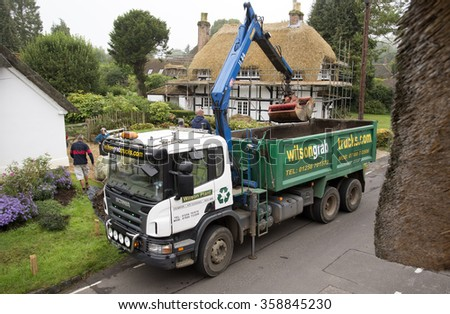 HAULAGE TRUCK WORKING IN AN ENGLISH VILLAGE - CIRCA 2015 -An overview of a grab truck with crane in action moving muck from a Hampshire village in southern England UK