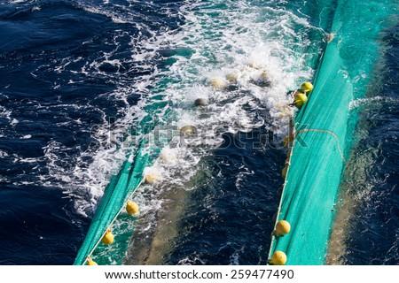 Hauling otter trawl fishing nets on the Atlantic Sea  - stock photo