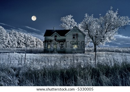 Haunted farmhouse under a full moon in infrared. - stock photo