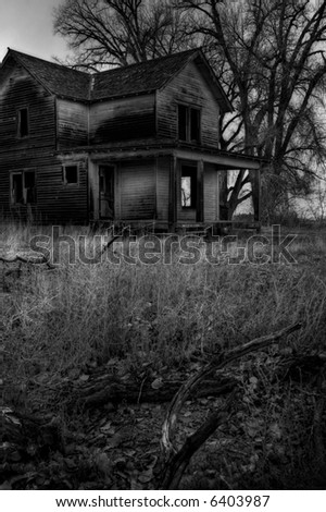 haunted house, a dark and moody image converted to monochrome with intentionally added grain to enhance mood - stock photo