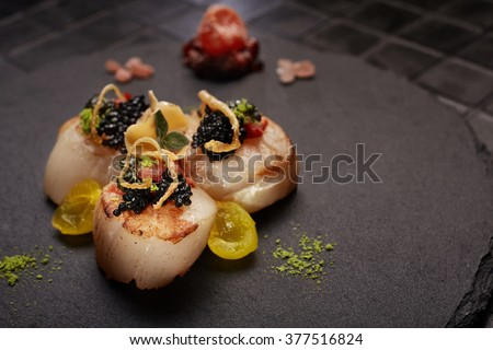 Haute cuisine 3 scallops served on black plate. Close-up.  - stock photo