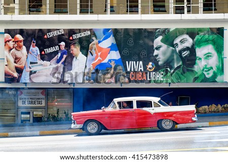 HAVANA,CUBA- APRIL 29,2016 :  An old classic car crosses in front of a billboard with revolutionary slogans in Havana - stock photo