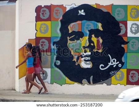 HAVANA, CUBA - APRIL 9, 2014: Cuban girls walking past a large mural of Che Guevara.  - stock photo