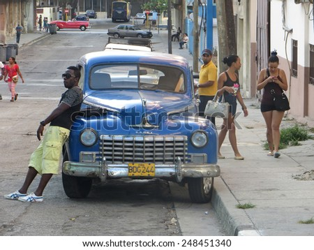 HAVANA, CUBA - APRIL 6, 2014: Cuban man leaning on an old car and two women walking by with a cell phone.  - stock photo