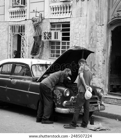 HAVANA, CUBA - APRIL 5, 2014: Cuban men leaning over the hood of an old car and a man up a ladder connecting an aerial.  - stock photo