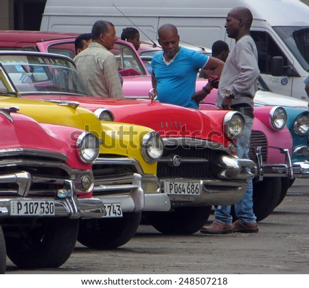 HAVANA, CUBA - APRIL 9, 2014: Drivers standing next to old cars waiting to drive tourists around Havana.                       - stock photo