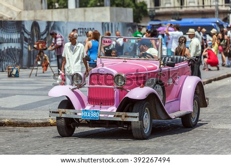 HAVANA, CUBA - APRIL 1, 2012: Really old pink antique car in front of Capitolio