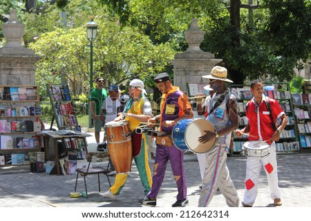 Havana, Cuba, August 10, 2012: Colorful Cuban girls dance on stilts and orchestra-man entertain tourists in front of the Palace of Fine Art, Old Havana - stock photo