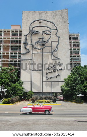 HAVANA, CUBA, AUGUST 16, 2016: Vintage car drives in front of iconic iron mural of Che Guevara's face on Ministry of Interior building, at the Revolution Square in Havana, Cuba