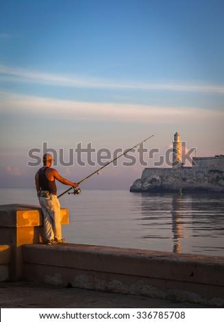 HAVANA, CUBA - CIRCA AUGUST, 2015: Cuban man fishing in front of the famous fortress of El Morro, Havana, Cuba - stock photo