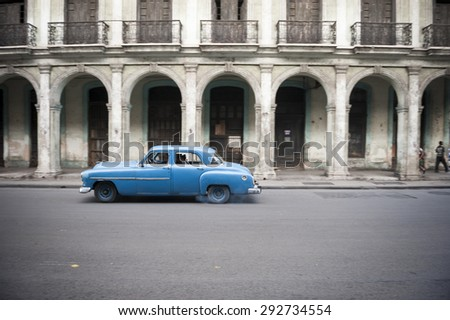 HAVANA, CUBA - CIRCA JUNE, 2011: Old American car drives in front of the traditional architecture of a colonial arcade. - stock photo
