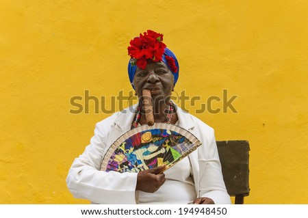 HAVANA, CUBA - DECEMBER 2, 2013: Old black lady dressed in typical cuban clothes smoking a huge cuban cigar against yellow wall iin the old quarter of Havana - stock photo