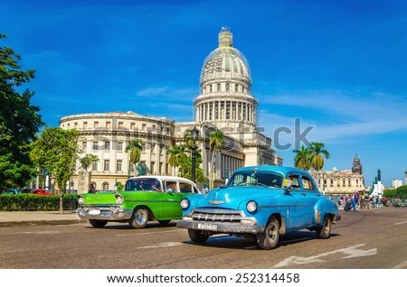 HAVANA, CUBA - DECEMBER 2, 2013: Old classic American cars rides in front of the Capitol. Before a new law issued on October 2011, cubans could only trade cars that were on the road before 1959.  - stock photo