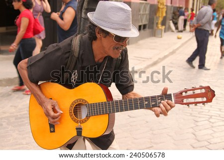 HAVANA,CUBA-FEB. 21,2014: A music man plays his guitar to tourists walking by downtown Havana Cuba  - stock photo