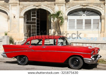 HAVANA, CUBA - FEBRUARY 24, 2011: Classic red car in Havana. Cuba has one of the lowest car-per-capita rates (38 per 1000 people in 2008).