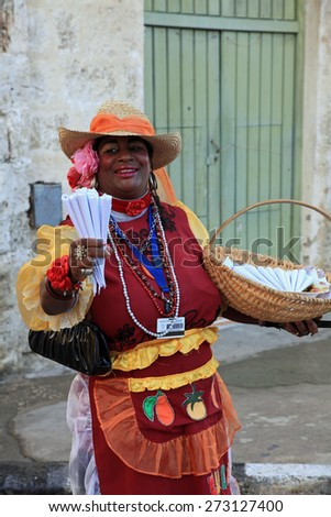 HAVANA, CUBA - FEBRUARY 11:  Cuban woman in colorful clothing selling sweets and peanuts on February 11, 2012 in old Havana, Cuba, for the entertainment of the tourists. - stock photo