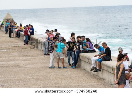 HAVANA,CUBA-FEBRUARY 9,2016:Tourist and locals sitting by The Malecon sea wall. Cubans sit in the area to relax from the city streess and to meet tourists visiting the Cuban capital - stock photo