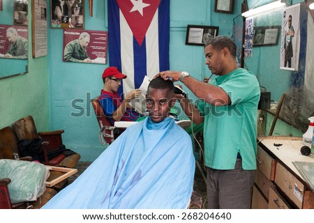 Havana, Cuba - 27 January, 2015: A man sits in a hairdresser chair while a hairdresser cuts his hair. In the back, a man waits, reading a newspaper