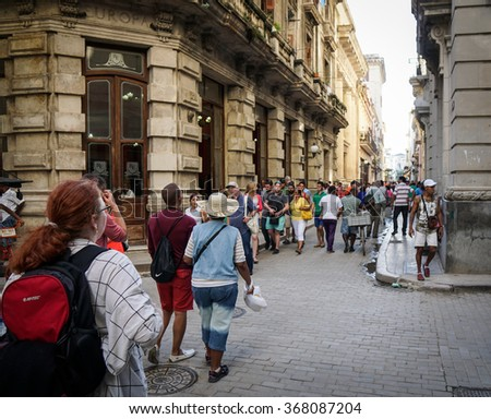 Havana, Cuba - January 5, 2016: Typical scene of one of streets in the center of La Havana - colonial architecture, people walking around - stock photo