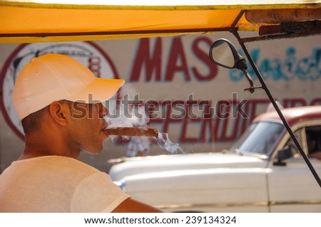 Havana, CUBA - JANUARY 20, 2013: Unknown young male taxi driver smoke cigar, in background old classic American car drive on street of Havana,CUBA on front of political slogan on wall. - stock photo