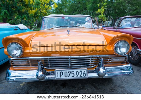 HAVANA,CUBA-JULY 12,2014: Old American cars for rent in central Havana. Due to scarcity,Cubans have kept old cars from 1950s running and nowadays is one important source of income