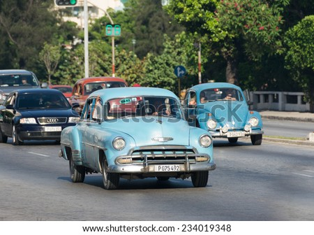 HAVANA,CUBA-JULY 3,2014: Old American cars running and making income for owners. The car supply limitations has made Cubans innovate to keep cars from the 50's running and make income with them.