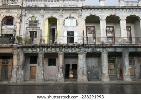 HAVANA, CUBA - JUNE, 2011: Cubans go about their daily lives against a background of classic colonial architecture on the facade of a crumbling building in central Havana.