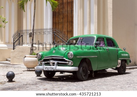 Havana, Cuba - June 11, 2014: Green classic cuban car parked in front of a colonial building in Old Havana