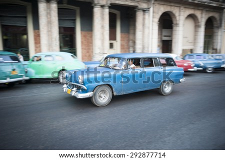 HAVANA, CUBA - JUNE, 2011: Old American car drives in front of the traditional architecture of a colonial arcade. - stock photo