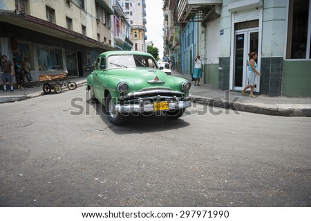 HAVANA, CUBA - JUNE, 2011: Vintage American car drives through an intersection in Central Havana.