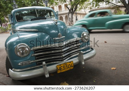 HAVANA, CUBA - JUNE, 2011: Vintage American car passes another parked on the Paseo del Prado street in Central Havana.